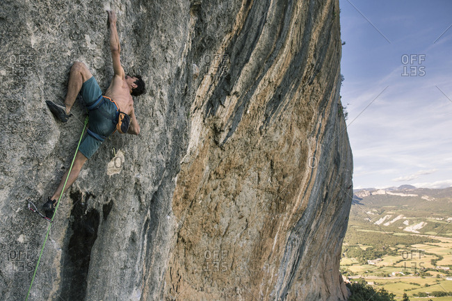 Low angle view of shirtless man rock climbing against sky