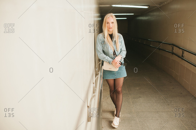 Full length portrait of young woman standing in underground walkway