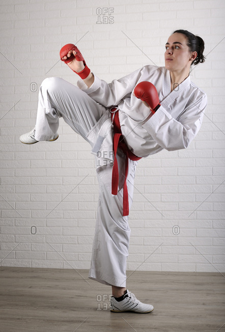 Full length of woman practicing karate against wall on hardwood floor