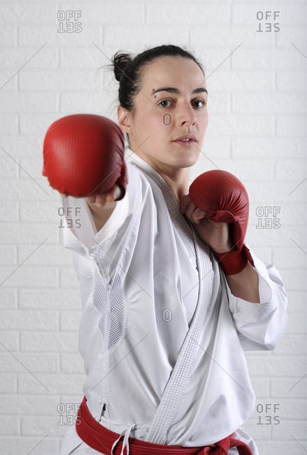 Portrait of confident woman practicing karate against wall