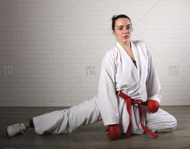 Portrait of confident woman practicing karate against wall on hardwood floor