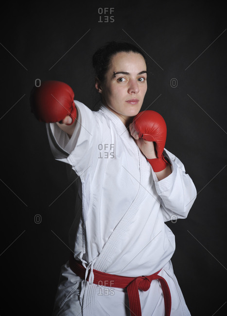 Portrait of woman wearing boxing gloves while practicing karate against black background