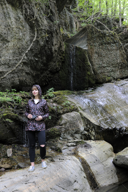 Full length of woman standing on rock in forest