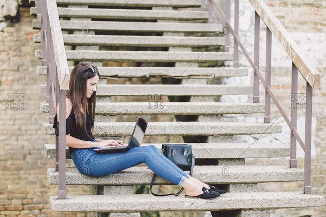 Side view of woman using laptop computer while sitting on steps