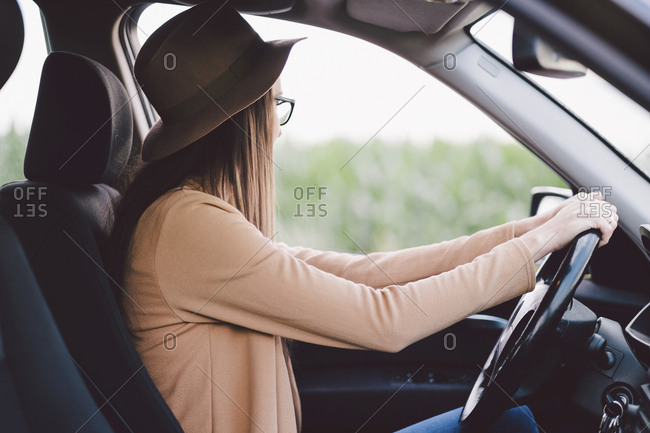 Side view of woman wearing hat while driving car