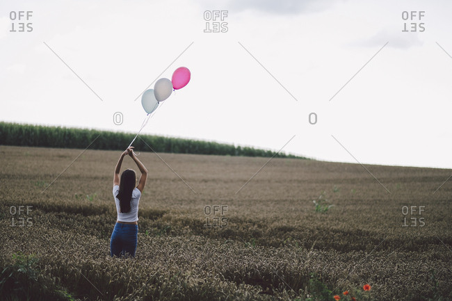 Rear view of woman holding balloons while standing against plants against sky