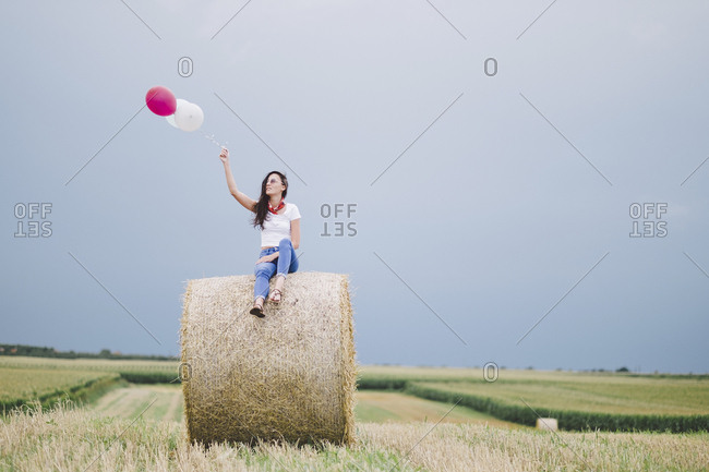 Woman holding balloons while sitting on hay bale against sky at farm