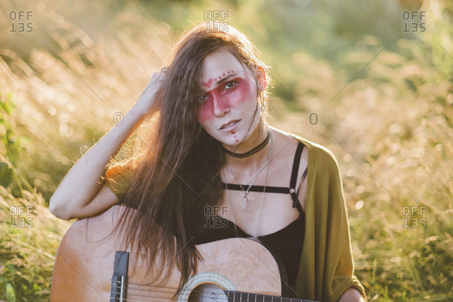 Portrait of woman with face paint sitting on grassy field during sunset