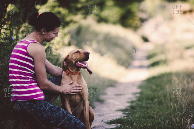 Side view of happy woman crouching with dog on grassy field at park