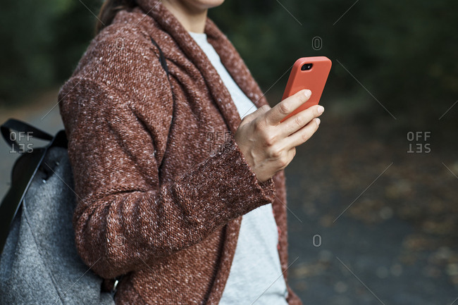 Midsection of woman using smart phone while standing in park during autumn