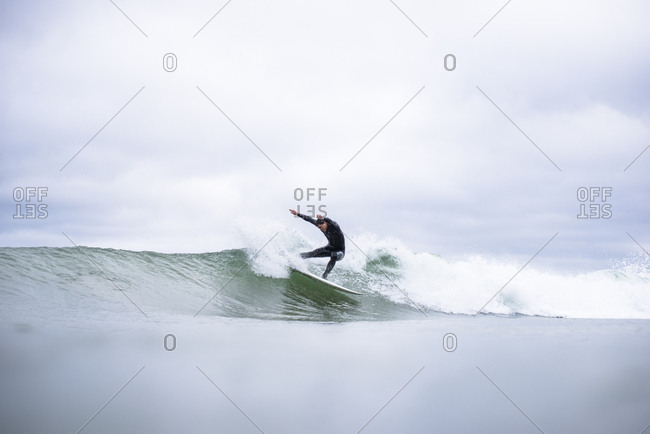 Man Surfing Waves on an Overcast Day