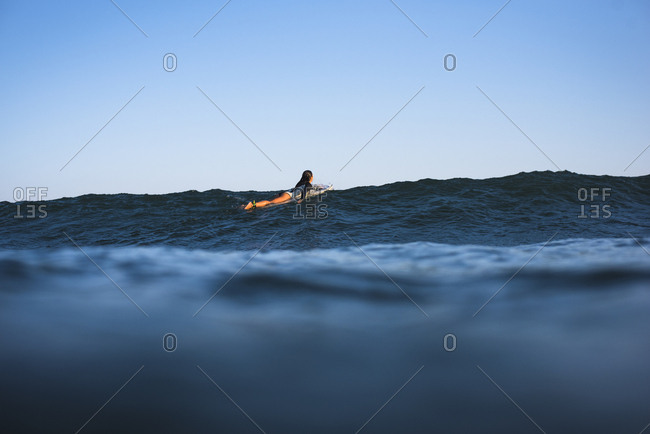 Young Woman Paddling out to Surf
