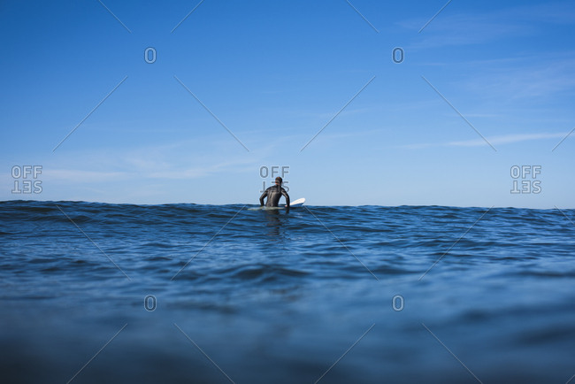 Man sitting in the Surf Lineup waiting for waves