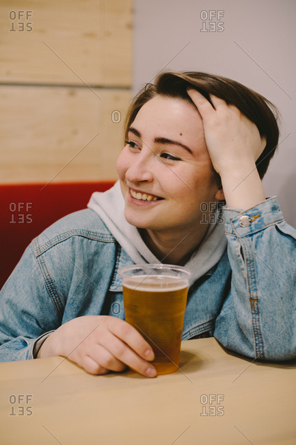 Happy woman having beer while sitting at table in restaurant