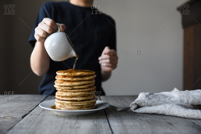 Cropped shot of a child pouring maple syrup on big stack of pancakes.