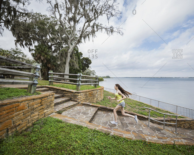 Side view of woman running on steps by river against cloudy sky at park