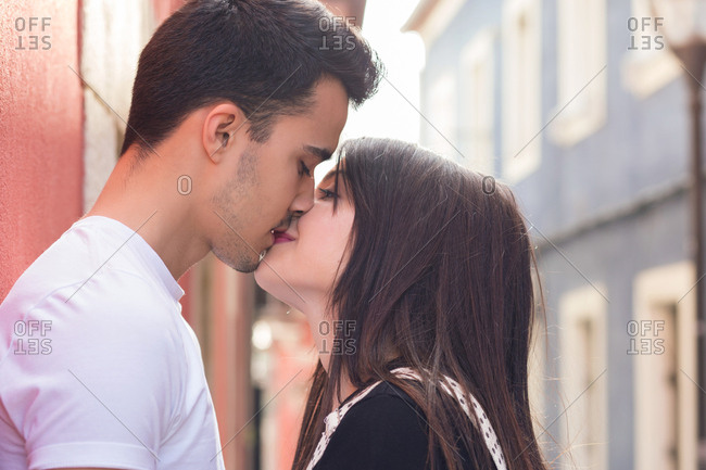 Side view of loving young couple kissing on mouth in city