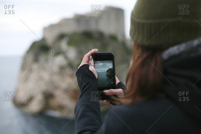 Looking over womans shoulder as she takes picture of cliff fortress