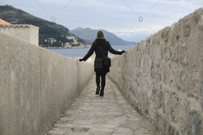 Low angle view of woman walking through narrow stone pathway outside.