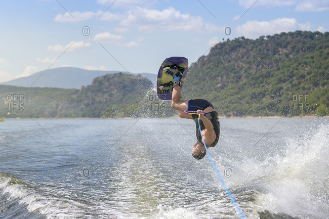 Man doing stunt while wakeboarding in sea against mountains during sunny day