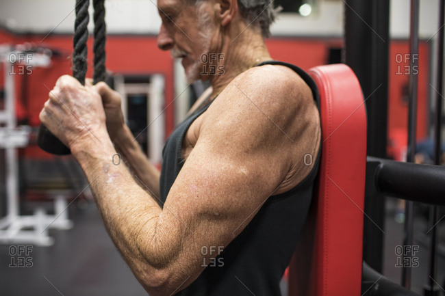 Fit Elderly man working out with triceps pulldown