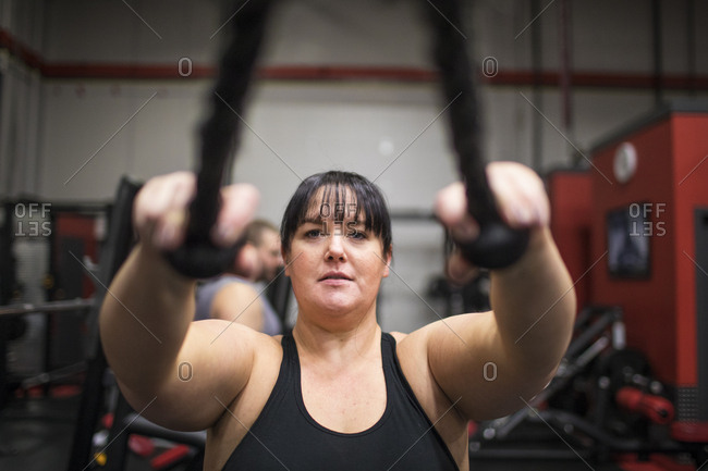 Strong woman training triceps muscle in gym