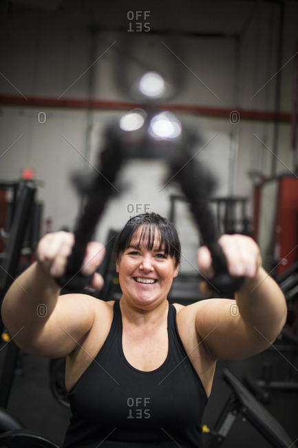 Smiling woman training triceps muscle in gym