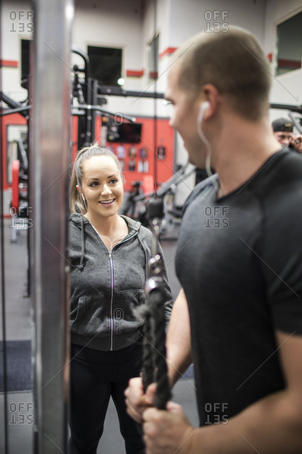 Attractive personal trainer works with client at the gym.