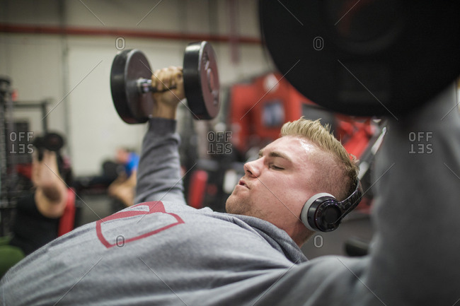 Weightlifter listens to music while training with dumbbells at the gym