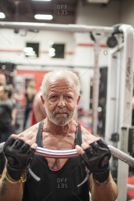 Fit elderly man training his biceps at the gym.