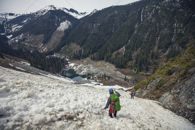 Two mountaineers descend avalanche chute on mountainside.
