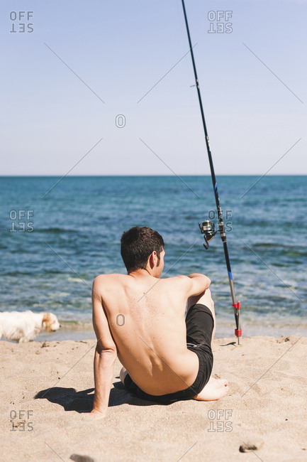 Rear view of shirtless man sitting on sand at beach with dog and fishing rod against clear sky during sunny day