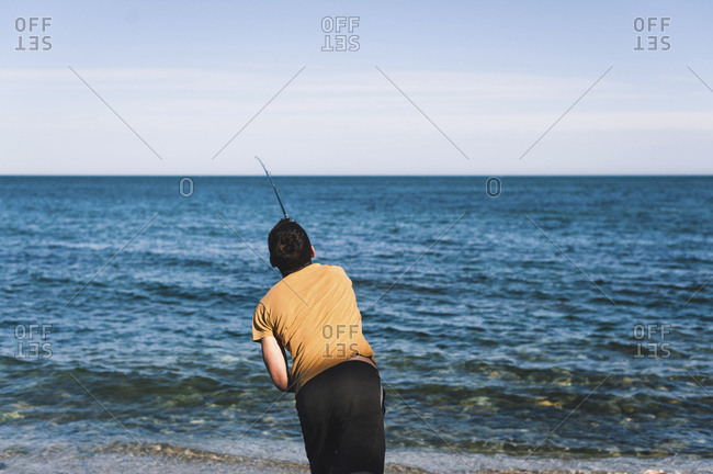 Rear view of man casting fishing line in sea against sky