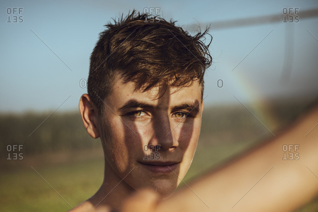 Boy cooling off with farm sprinklers in a field of corn