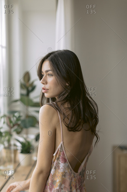 Woman in nightgown looking over her shoulder.