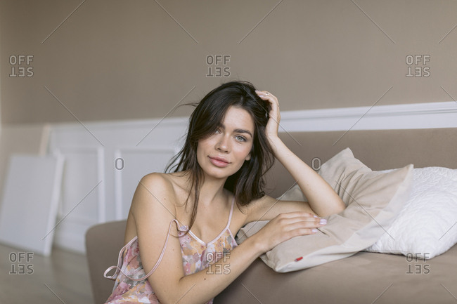 Woman in nightgown sitting on the floor leaning against couch.
