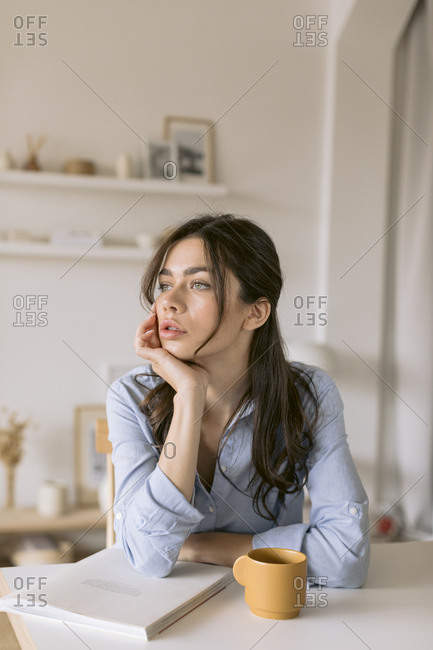 Woman sitting at table with a cup of coffee and a magazine pondering.