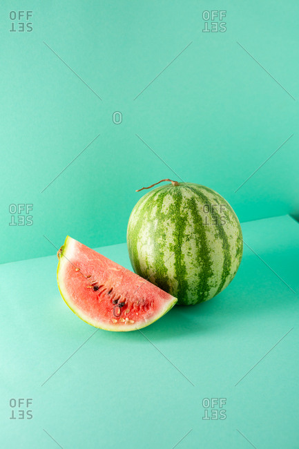 Whole Watermelon and slice on green background