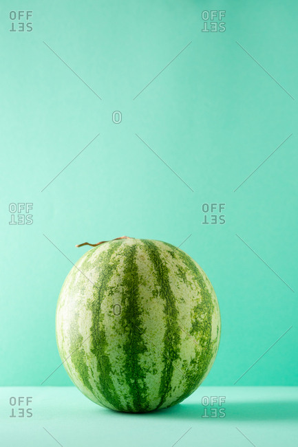 Whole Watermelon sitting on turquoise table