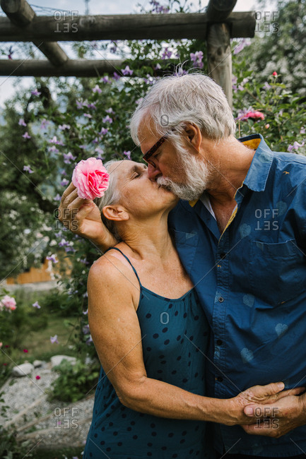 An older couple shares a kiss in a rose garden