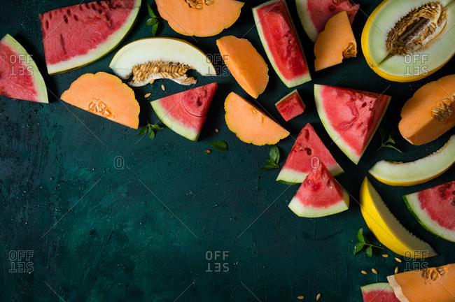 Slices of watermelon, cantaloupe and canary melon with fresh mint