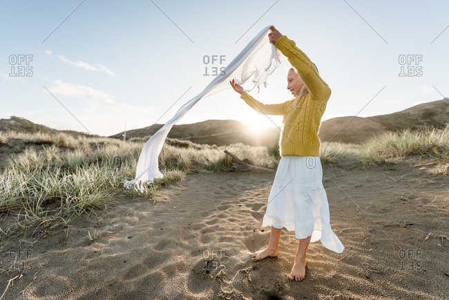 Girl plays with her scarf on the beach