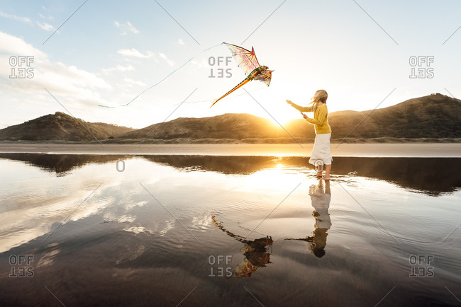 Girl flies a kite on the beach at sunset