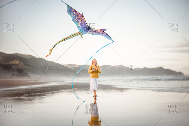 Girl happily flying a kite on the beach