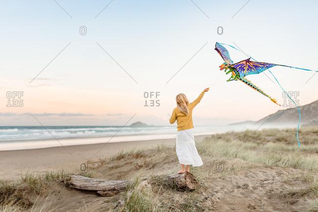 Girl flies her kite on the coast
