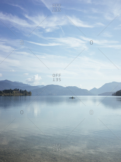 Scenic view of calm lake by silhouette mountains against blue sky during sunny day in Walchensee
