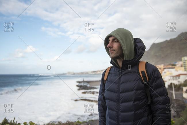 Male traveler looking away against the Atlantic Ocean and cloudy sky