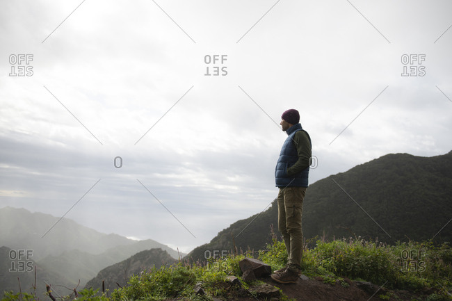 Thoughtful Man Looking At Mountain Landscape From Cliff Against Sky