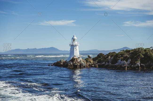 Lighthouse by Gordon River against blue sky