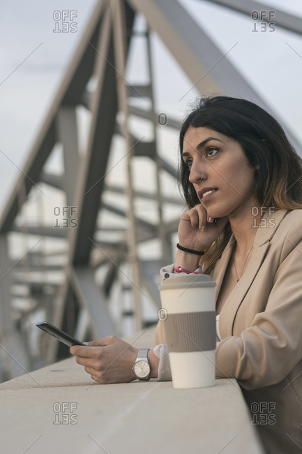 Businesswoman with coffee cup using smart phone while standing on bridge during sunset